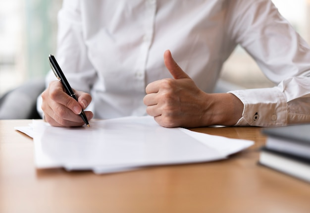 Mujer escribiendo y mostrando los pulgares para arriba