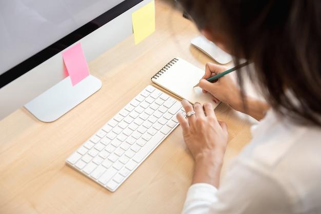 Mujer escribiendo nota en papel en la mesa de la oficina