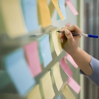 Mujer escribiendo en notas adhesivas en la ventana de la oficina