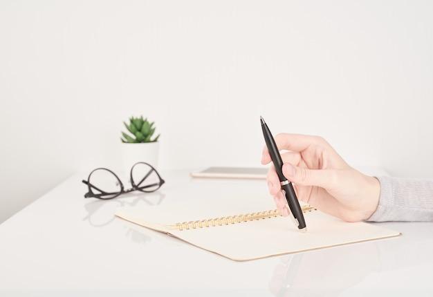 Mujer escribiendo en la página del cuaderno,
