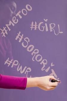 Mujer escribiendo palabras con hashtags en espejo