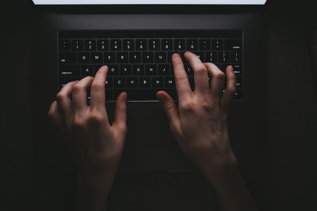 Mujer está escribiendo en un teclado de computadora portátil