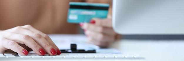 Mujer escribiendo en el teclado de la computadora y sosteniendo la tarjeta bancaria en sus manos closeup
