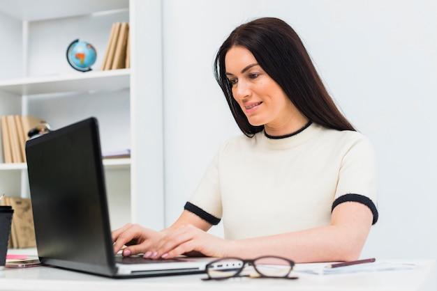 Mujer escribiendo en el teclado del ordenador portátil en la oficina