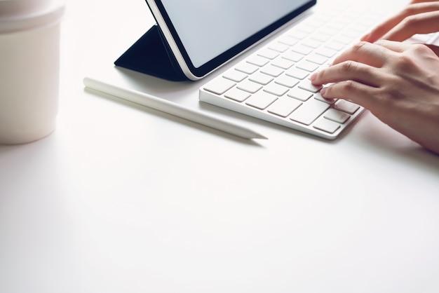 Mujer escribiendo teclado portátil y pantalla de tableta en blanco sobre la mesa