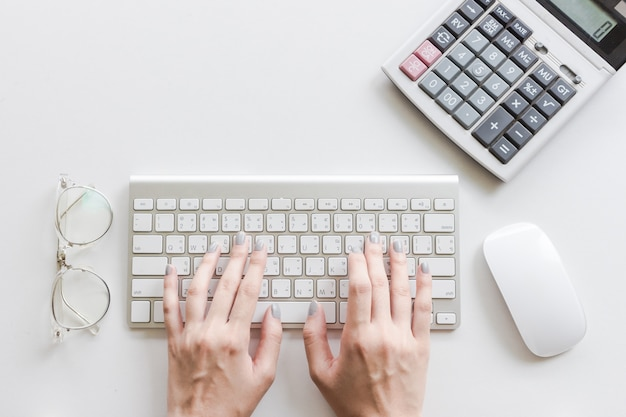Mujer escribiendo en el teclado, usando calculadora, gafas y mouse