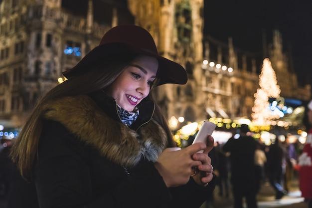 Mujer escribiendo en el teléfono en el mercado de navidad en munich
