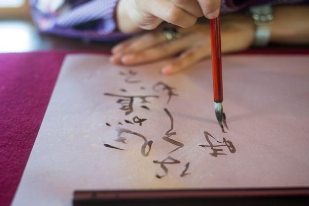 Mujer escribiendo con tinta sobre papel japonés