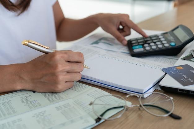Mujer escribiendo y usando calculadora, cuenta y concepto de ahorro.