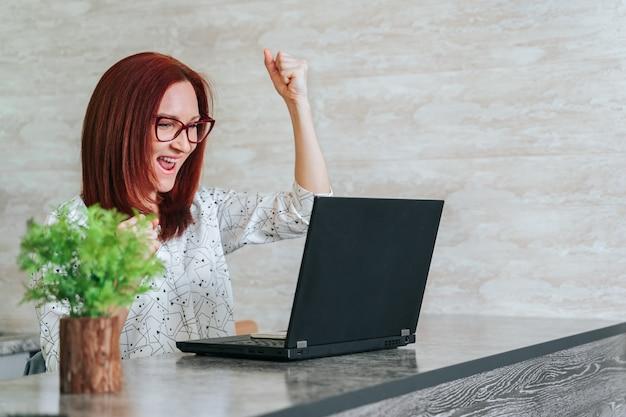 Mujer en el escritorio de oficina con laptop sintiéndose genial en el horizonte profesional