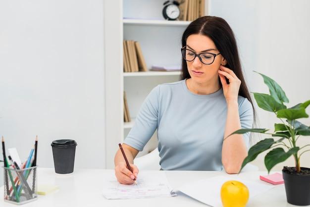 Mujer, escritura, en, papeles, en la mesa