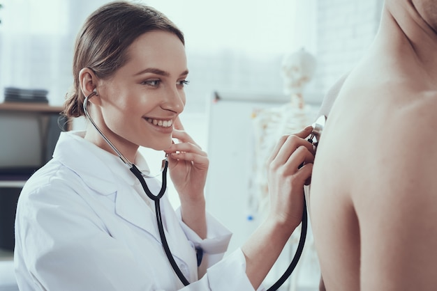 Mujer escucha los pulmones con estetoscopio.