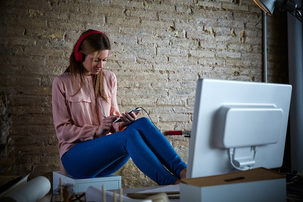 Mujer escuchando auriculares de música móviles en la oficina