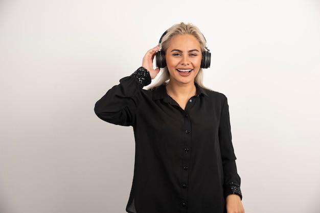 Mujer escuchando la canción con auriculares sobre fondo blanco. foto de alta calidad