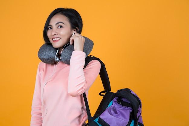 Mujer escuchando música con almohada para el cuello y mochila