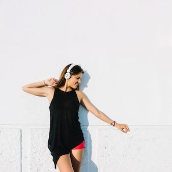 Mujer escuchando música en auriculares frente a la pared