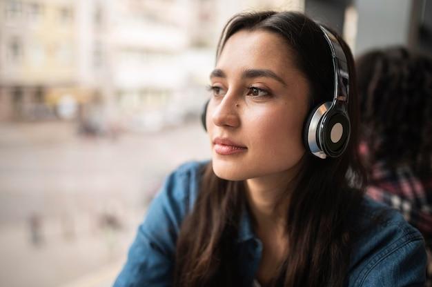 Mujer escuchando música en auriculares con su amiga en la parte de atrás