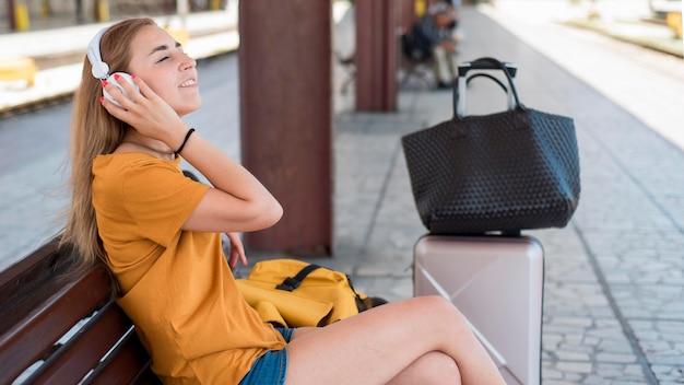 Mujer escuchando música en un banco en la estación de tren