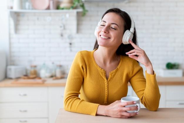 Mujer escuchando música en la cocina