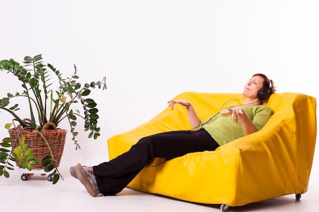 Mujer escuchando música y descansando en el sofá