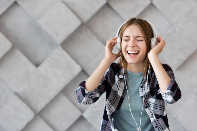 Mujer escuchando música con espacio de copia
