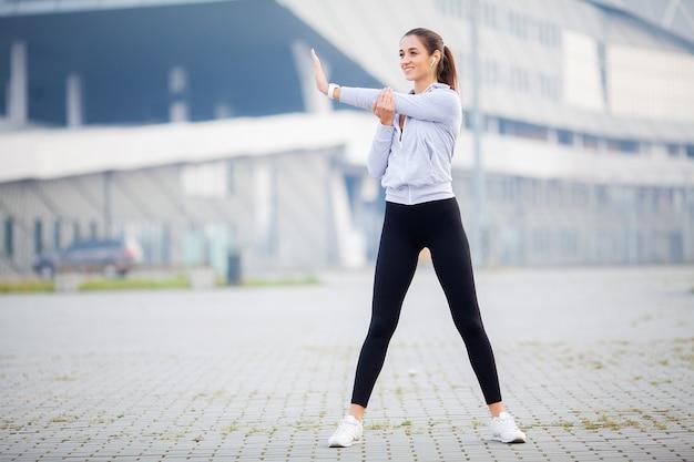 Mujer escuchando música, haciendo ejercicios de entrenamiento en la calle