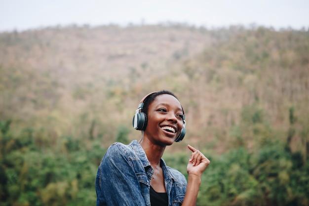 Mujer escuchando música en la naturaleza.