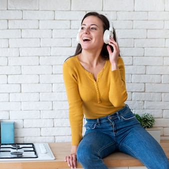 Mujer escuchando música y sentada en mostrador