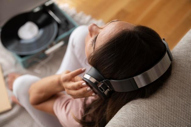 Mujer escuchando música a través de auriculares en casa