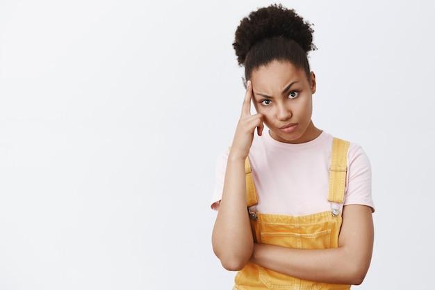 Mujer escuchando quejarse de un cliente molesto, mirando intensamente, frunciendo el ceño y frunciendo los labios, siendo seria y molesta, sosteniendo el dedo índice en la sien, de pie sobre una pared gris
