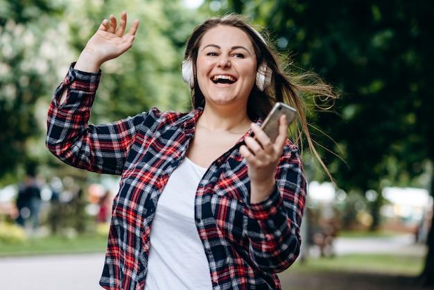 Mujer escuchando su música favorita a través de auriculares, en medio de la calle, al aire libre