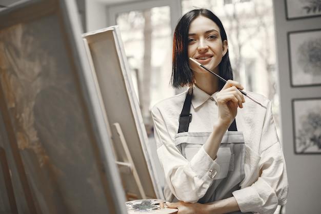 Mujer en una escuela de arte con un delantal.