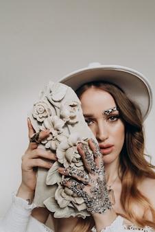 Mujer con escultura de arcilla en sus manos