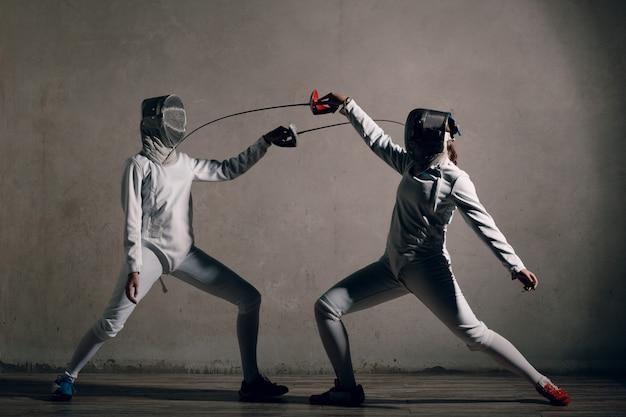 Mujer esgrimista con espada de esgrima. fencers duel.