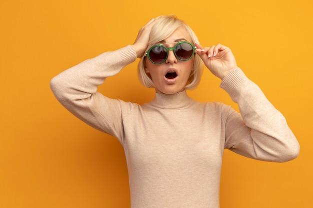 Mujer eslava rubia bastante sorprendida en gafas de sol pone la mano en la cabeza en naranja