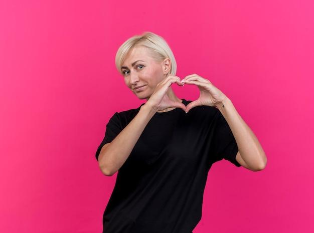 Mujer eslava rubia de mediana edad complacida mirando al frente haciendo signo de corazón aislado en la pared rosa con espacio de copia