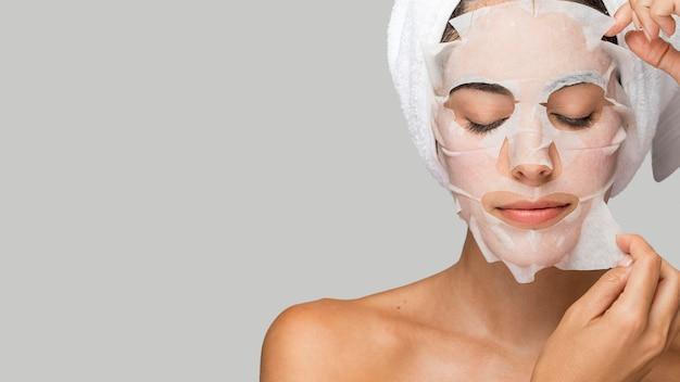 Mujer con espacio de copia de máscara de belleza facial