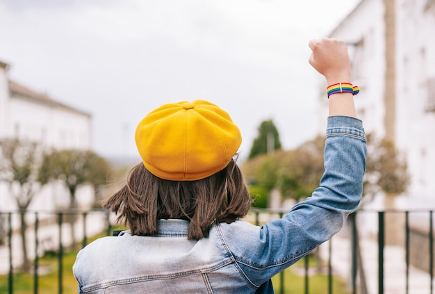Mujer de espaldas con las manos arriba y pulsera de arco iris lgbt, foto vertical