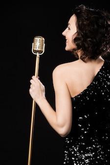 Mujer de espaldas con un micrófono