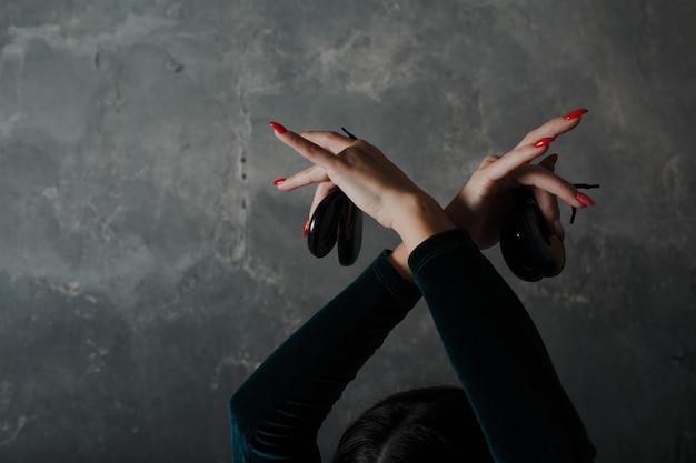 Mujer española adulta joven bailando flamenco con castañuelas sobre fondo gris vintage