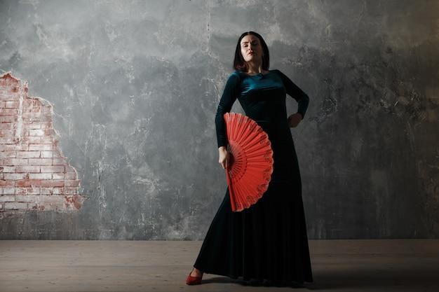 Mujer española adulta joven bailando flamenco sobre fondo gris vintage