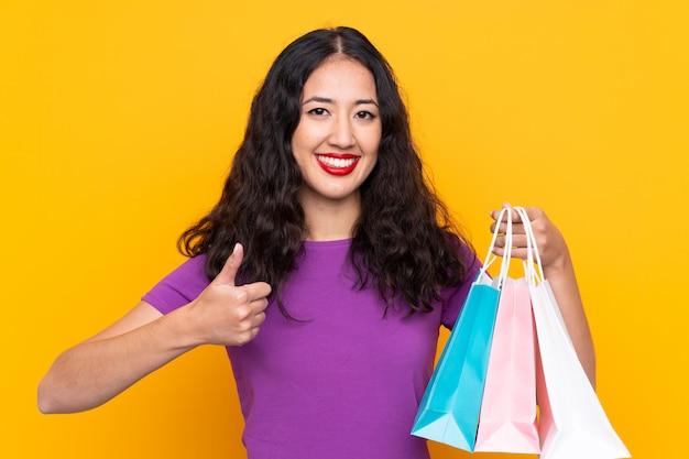 Mujer española china con bolsa de compras con el pulgar hacia arriba porque algo bueno ha sucedido