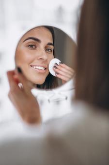 Mujer con espejo quitando maquillaje con almohadilla