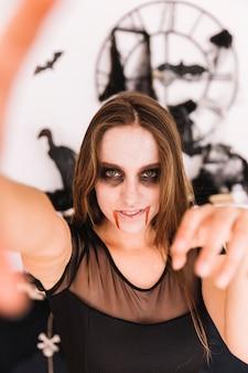 Mujer con espeluznante halloween sombrío delante de la pared con murciélagos