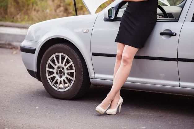Una mujer espera ayuda cerca de su automóvil averiado en el lado de la carretera