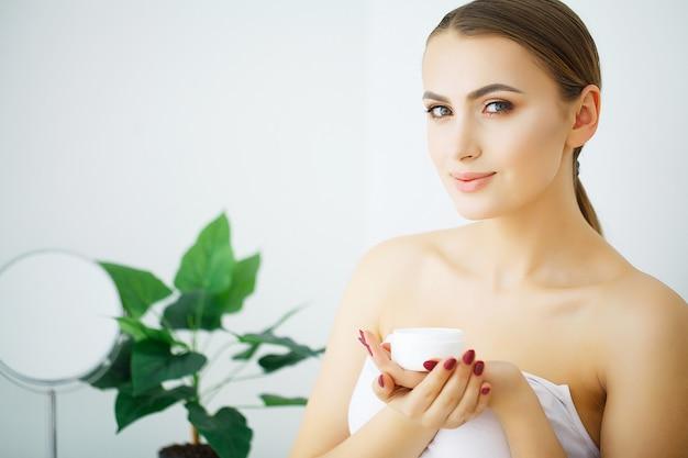 Mujer espera crema cosmética, bello rostro joven modelo,