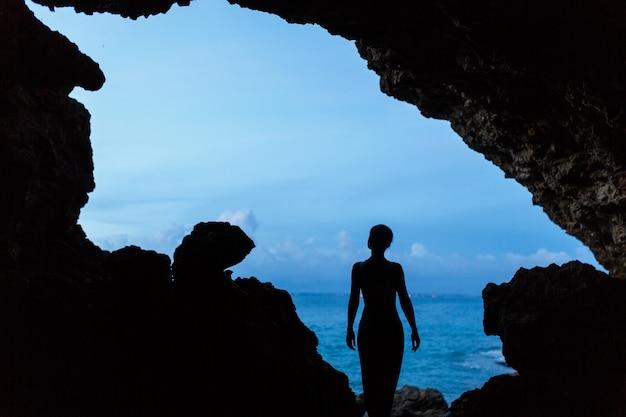 Mujer espera puesta de sol en la cueva balinesse en ocean beach