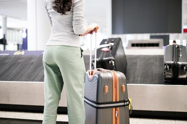 Mujer esperando el equipaje de la cinta transportadora en el aeropuerto