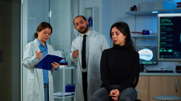 Mujer esperando médico sentado en una silla en el laboratorio de investigación neurológica, mientras que el equipo de investigadores discute en segundo plano el estado de salud del paciente, funciones cerebrales, sistema nervioso, tomografía