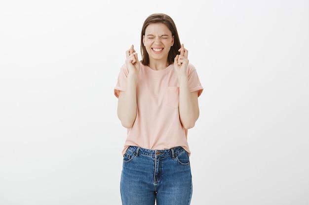 Mujer esperanzada emocionada que desea, cruzar los dedos buena suerte